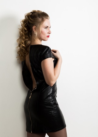 Beautiful young woman wearing short leather black dress with naked back on a light background Archivio Fotografico
