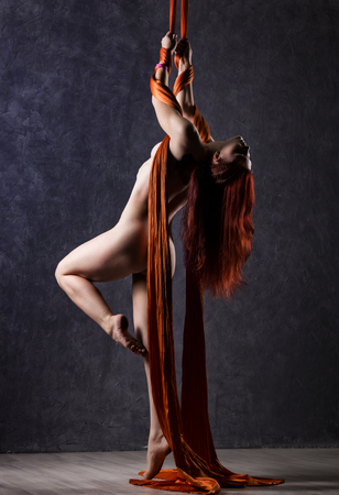 Beautiful nude dancer on aerial silk, graceful contortion, acrobat performs a trick on a ribbons