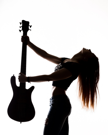 silhouette of rock woman playing on electric guitar on a white background. Foto de archivo