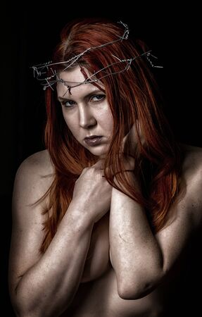 sexy beautiful woman with a wreath of barbed wire on the head on a dark background