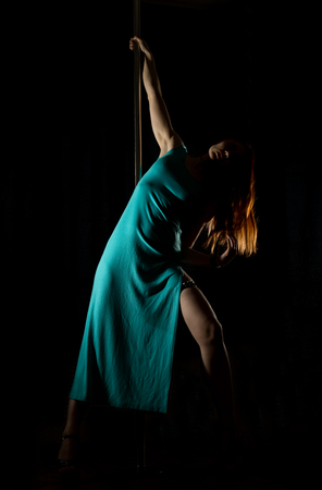 sexy woman pole dancer in a long turquoise dress with a slit on a dark background Stock Photo