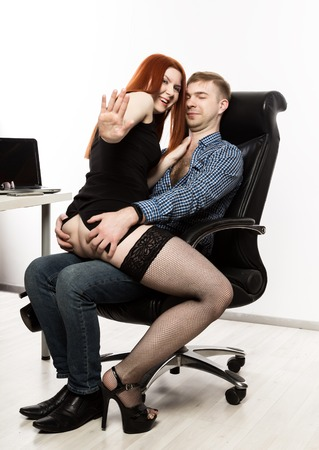 young sexy secretary is sexually harassing to her boss. love affair at work. accidentally caught Stock Photo