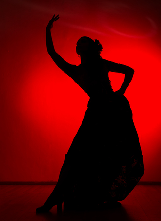 silhouette of spanish girl flamenco dancer on a red background