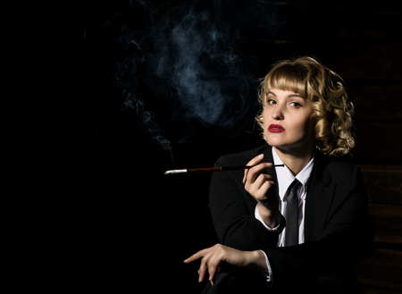 businesswoman with cigarette on a dark background, stylized retro portrait 版權商用圖片