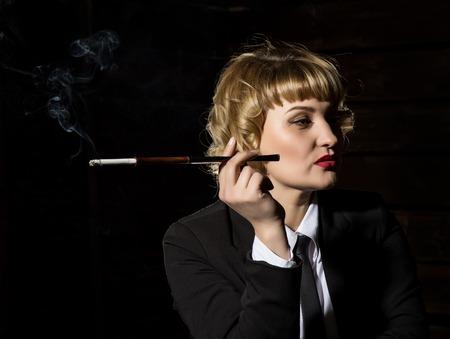 businesswoman with cigarette on a dark background, stylized retro portrait 스톡 콘텐츠
