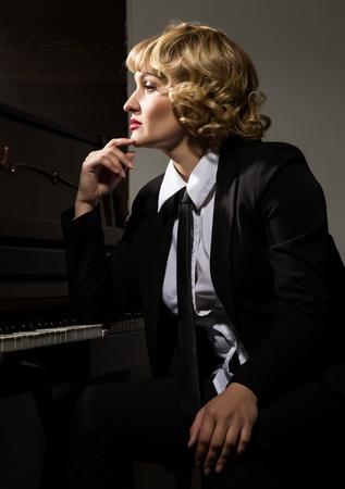 Professional female musician sitting near piano
