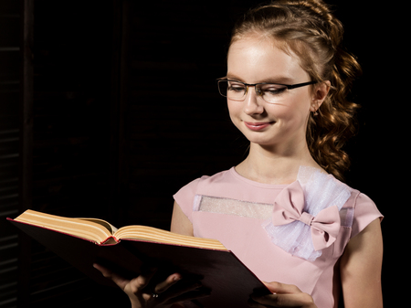 Lovely little girl standing and reads book over dark background