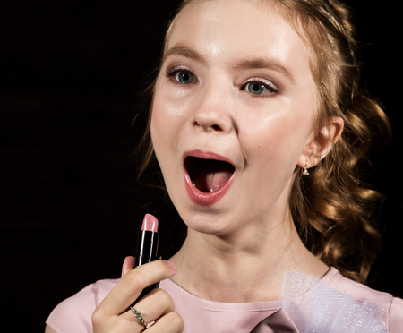 small beauty painting her lips of pink lipstick on a dark background Stock Photo
