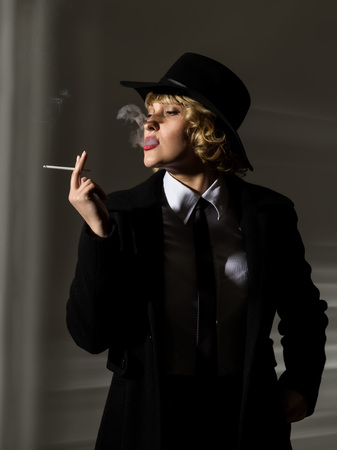 businesswoman with cigarette on a dark background, stylized retro portrait Stock fotó