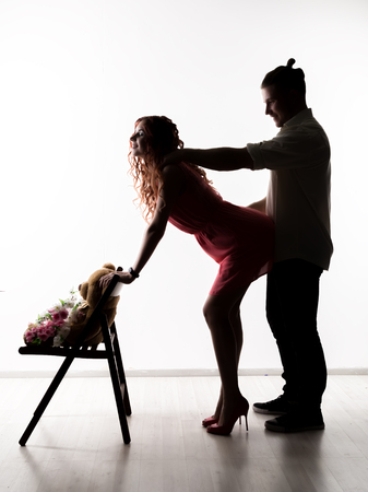 silhouette of lovely beautiful couple standing and hugging in a studio. Intimate moments romantic lovers Foto de archivo