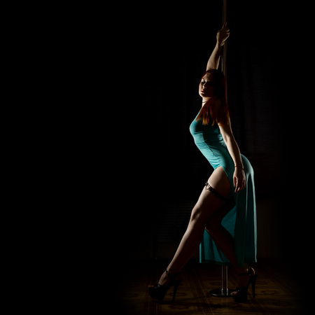 Gorgeous sexy dancer in night club. woman in a long turquoise dress with a slit on a dark background. free space for your text Stock Photo