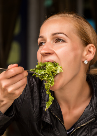 businesswoman eating salad in an outdoor cafe. Healthy lifestyle: girl eating green tasty food