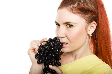 Beautiful redhead woman is eating black grapes. concept of healthy eating