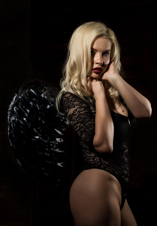 fallen black angel with wings. Sexual woman in black bodysuit and black wings on a black background. Stock Photo