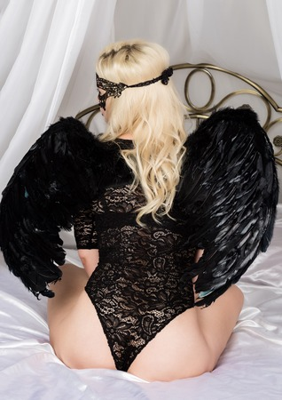 Fallen black angel with wings. Sexual woman in black bodysuit and black wings on a white background.