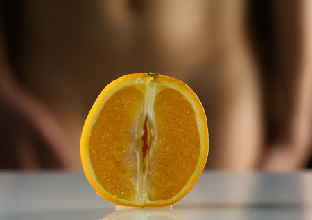 close-up half orange, woman takes off her panties on a dark background. imitation vagina. Stock fotó