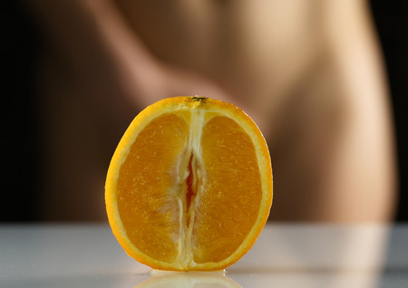 close-up half orange, woman takes off her panties on a dark background. imitation vagina. 스톡 콘텐츠