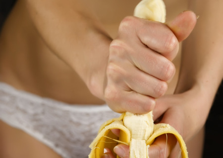 Young woman in a white panties squeezes banana in her hands. close-up buttocks and hip. Foto de archivo