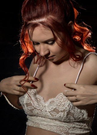cheerful redhead girl in a transparent blouse with curly hair smiling on a dark background.