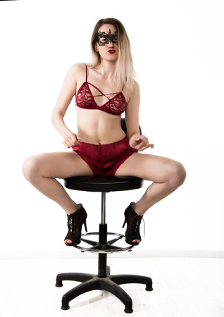 Sexy elegant woman in red lingerie is posing while sitting on a high chair and spreading her legs. girl on a white background