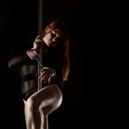 beautiful redhead woman in lingerie dancing near the pilon with handcuffs. exotic pole dance Banque d'images