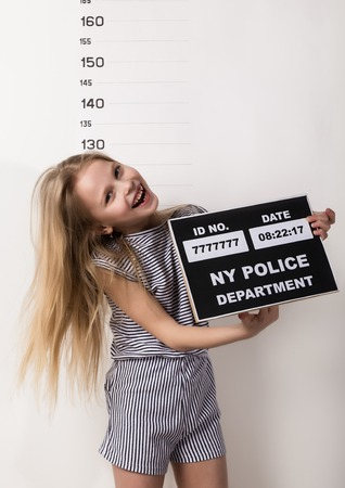 Young beautiful blonde child with a sign, Criminal Mug Shots. difficult children, social tension