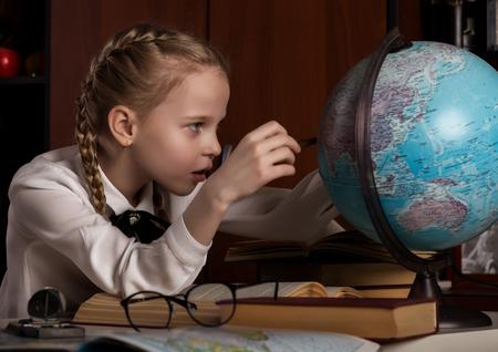 Schoolgirl doing homework, little blonde girl studing at home at the table. childrens education Standard-Bild