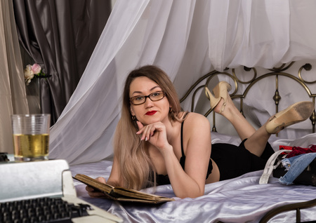 seductive young woman lying on the bed and reading a book. beautiful female writer is resting, retro typewriter nearby in the foreground