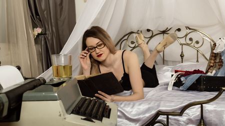 seductive young woman lying on the bed and reading a book. beautiful female writer is resting, retro typewriter nearby in the foreground Archivio Fotografico