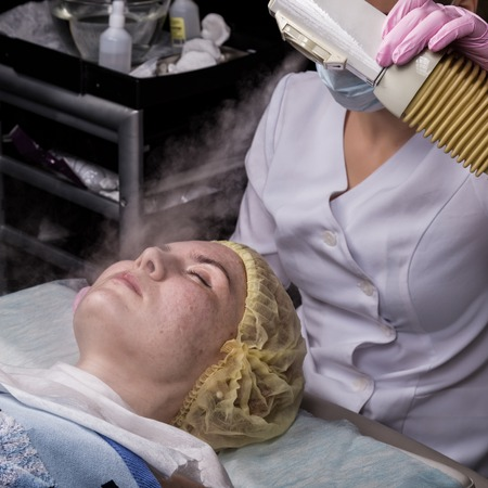 Doctor cleanses the womans skin with a steam. young woman with problem skin at the beautician. Cosmetology concept Imagens