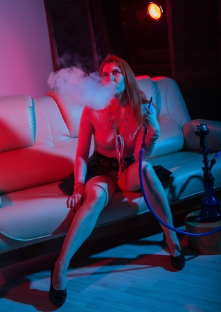 Sexy redhead woman vaping electronic hookah in red blue tones