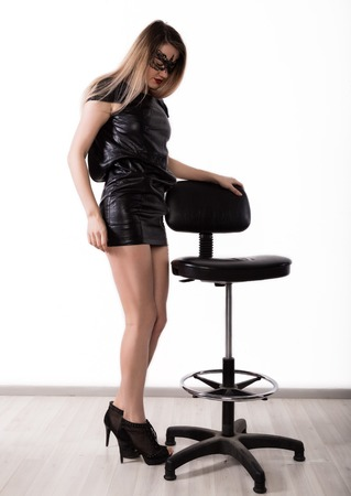 Sexy seductive womanin a little leather black dress and lace mask is dancing near the high chair. girl on a white background