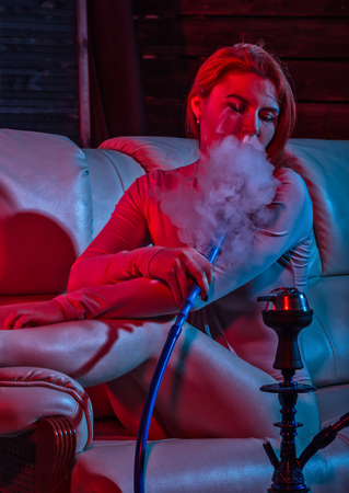 Sexy redhead woman vaping electronic hookah in red blue tones. girl blows white doom