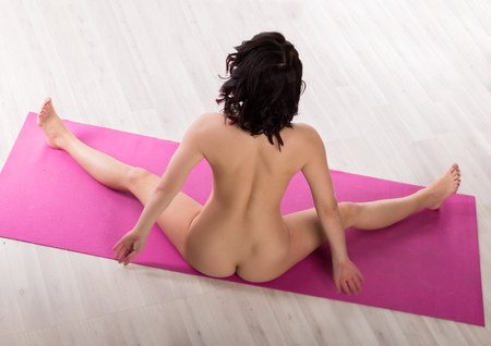 young seductive woman performs exercises in the nude. athletic woman on a light background