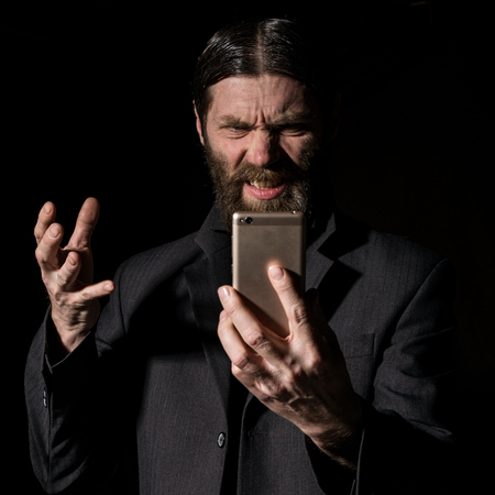 Old believer senior priest with a smartphone, bearded old man is calling on a dark background Standard-Bild - 124429393