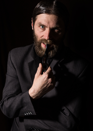 vintage handsome bearded man with a smoking pipe on a dark background Standard-Bild - 124450428