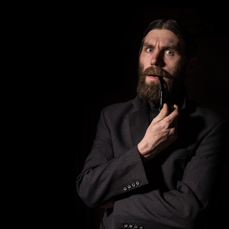 vintage handsome bearded man with a smoking pipe on a dark background. free space for your text Standard-Bild - 124450429