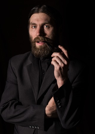vintage handsome bearded man with a smoking pipe on a dark background