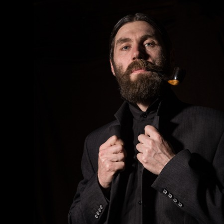 vintage handsome bearded man with a smoking pipe on a dark background. free space for your text