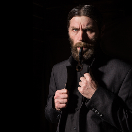 vintage handsome bearded man with a smoking pipe on a dark background. free space for your text Standard-Bild - 124446864