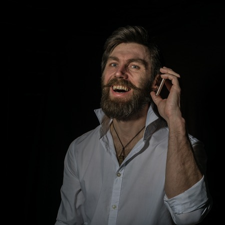 handsome bearded man using his phone with smile on a dark background Standard-Bild - 124446865