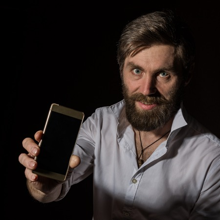 handsome bearded man shows his phone with fascinating smile on a dark background. Standard-Bild - 124446868