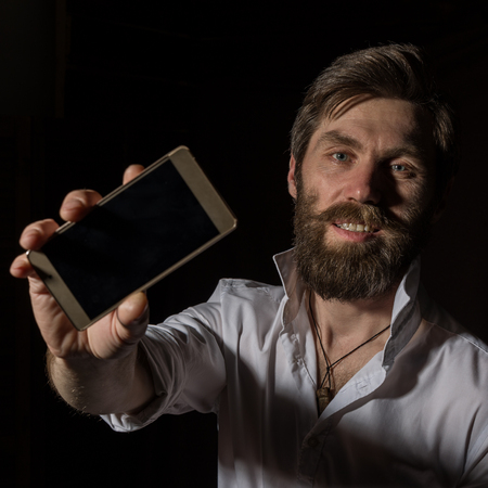 handsome bearded man shows his phone with fascinating smile on a dark background. Standard-Bild - 124446870