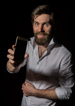 handsome bearded man using his phone with smile on a dark background Standard-Bild - 124446886