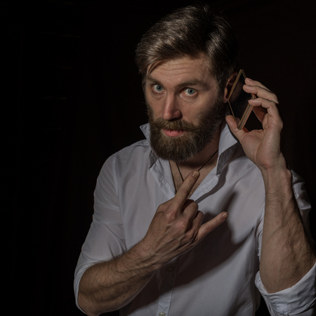 handsome bearded man using his phone with smile on a dark background Standard-Bild - 124446888