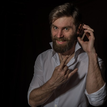 handsome bearded man using his phone with smile on a dark background Standard-Bild - 124446890