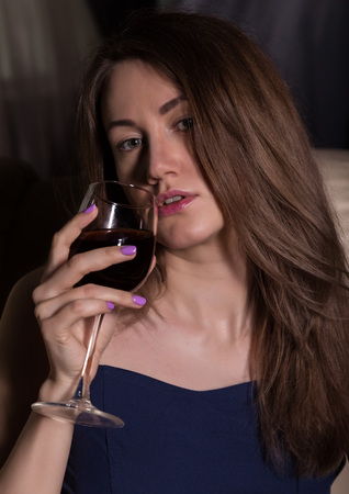 close-up of charming young woman drinks red wine Standard-Bild - 124446942