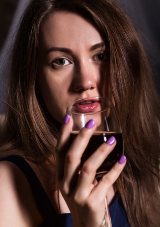 close-up of charming young woman drinks red wine Standard-Bild - 124446947