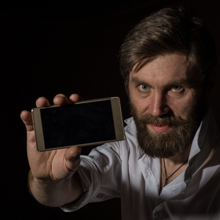 handsome bearded man shows his phone with fascinating smile on a dark background.