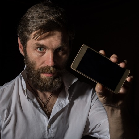 handsome bearded man shows his phone with fascinating smile on a dark background. Standard-Bild - 124446951